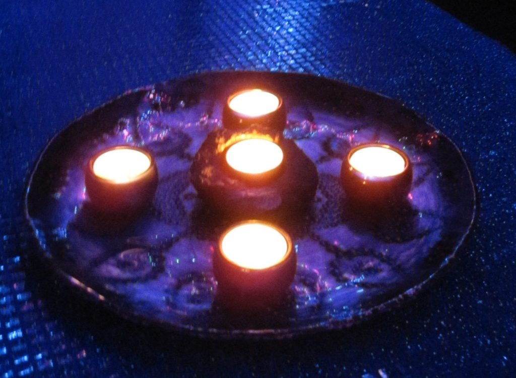 five candles intersecting on a dark background